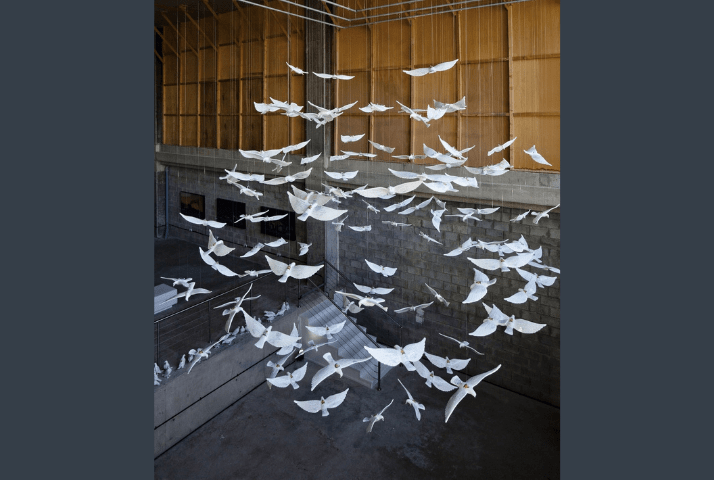 """Suspended Together"""" by Manal Al-Dowayan. Arrangement of ceramic doves in flight , some suspended from the ceiling with strings, some on the floor"""