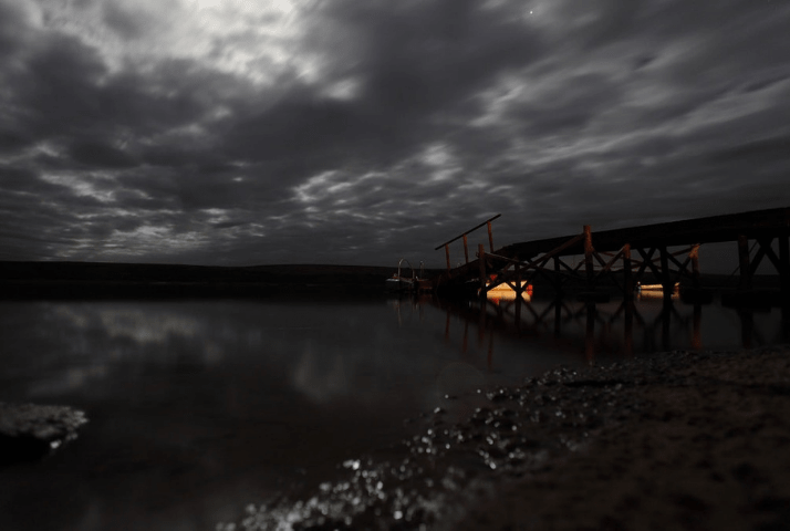 Scene showing river in the dark, bridge, and lights from boats in the distance