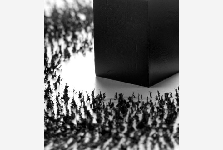 Artwork with central black magnet attracting iron filings, representing Makkah