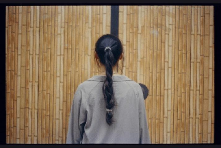 Back of girl's head showing long braid folded inward at the base